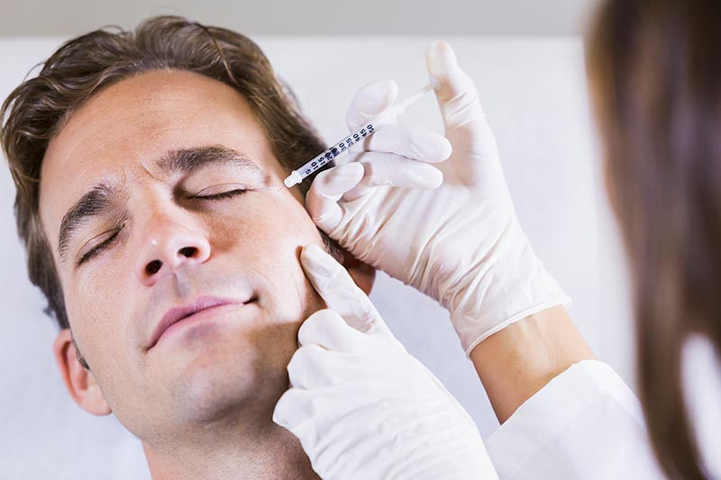 Man receiving non surgical cosmetic injection around his eye
